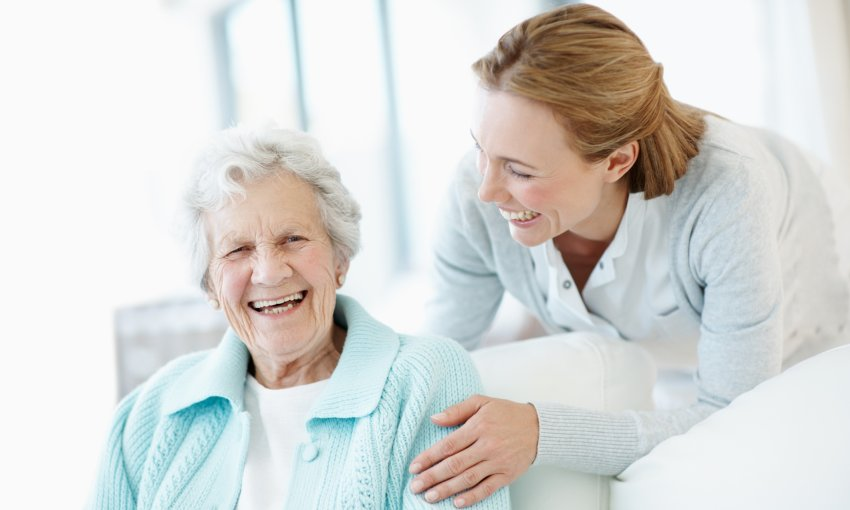 caregiver and mature woman smiling