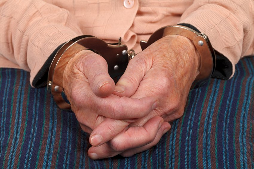elderly woman in handcuffs