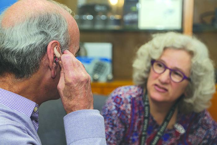 older adult testing hearing aid