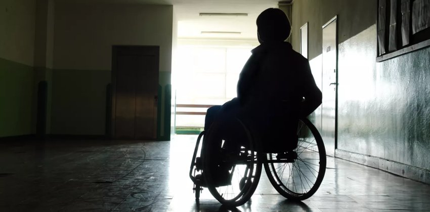 patien on wheelchair against door