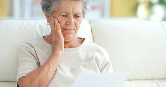 upset elderly woman reading letter